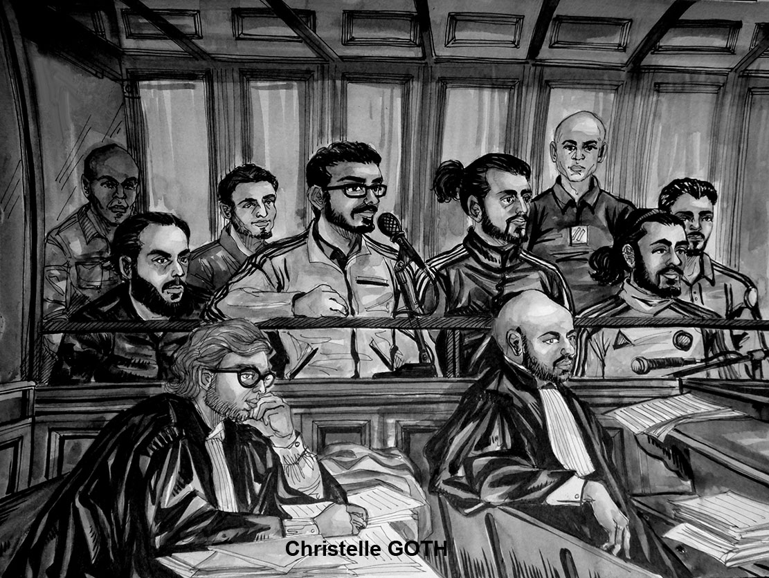 Benoît Roussillon, debout à droite dans le box, barbe courte, cheveux en catogan, survêtement sombre, comparaît aux côtés de 4 autres prévenus. Deux avocats sont assis au premier plan, devant le box.